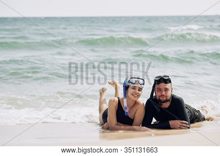 Beautiful Smilng Boyfriend And Girlfriend Resting On Beach After Snorkeling In Sea