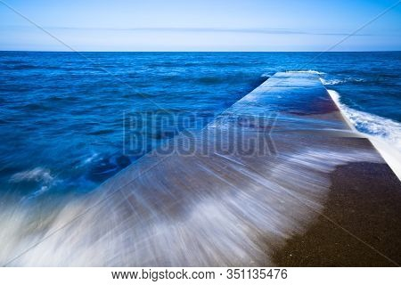 Stunning Landscape Of A Long Pier And A Hectic Sea On A Summer Evening. Concept Of Natural Elements