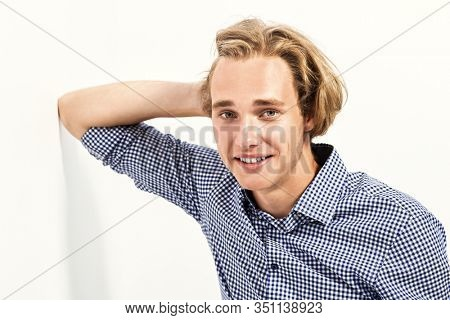 A portrait of a goodlooking young man in a checked shirt posing indoor. Men fashion, beauty, optics.