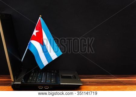 Flag Of Cuba , Computer, Laptop On Table And Dark Background
