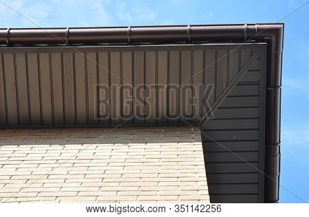 House Rooftop Corner With Soffit Boards And Rain Gutter Pipeline