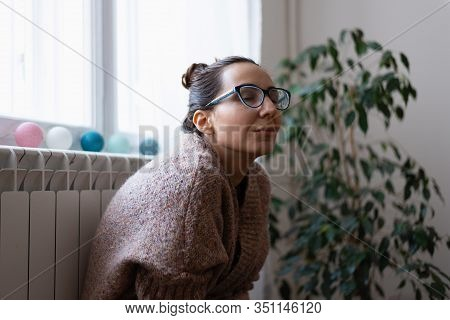 Woman Relaxing At Home. Domestic Lifestyle. Woman Keeping Warm At Home Close To Radiator. Modern Lif