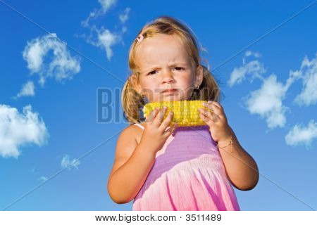 Little Girl Eating Cooked Sweet Corn