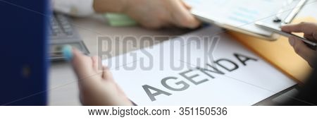 Close-up Of Human Hand Pointing At Diagram Paper During Explanation. Agenda Sign Laying On Desktop.