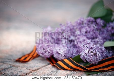Lilac With St. George Ribbon On A Marble Slab. Flowers In Memory Of The Soviet Soldiers Who Died Dur