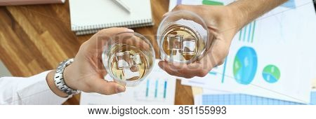 Top View Of Glassful With Alcoholic Beverage With Ice-cubes In Male Hands. Colleague Sitting At Tabl