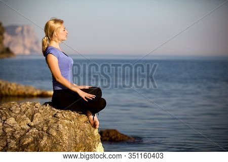 Young Relaxed Caucasian Woman Sits On A Stone And Enjoys The Rays Of The Summer Sun On The Backgroun