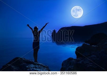 Rear View Unidentified Young Happy Woman Stands On A Stone Raise Hands Up Looking At The Big Moon An