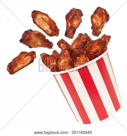 Perfect chicken wings flying around from big red white stripes bucket box