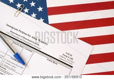 I-140 Immigrant Petition For Alien Workers Blank Form Lies On United States Flag With Blue Pen From