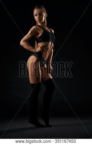 Full Length Side Portrait Of Sexy Caucasian Female Model With Ponytail Wearing Black Lingerie And Kn