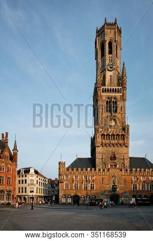 Belfry tower famous tourist destination and Grote markt square in Bruges, Belgium on sunset