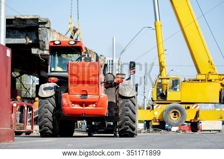 Constuction Site Heavy Machinery Industrial Background. Telescopic Handler Vehicle And Big Mobile Cr