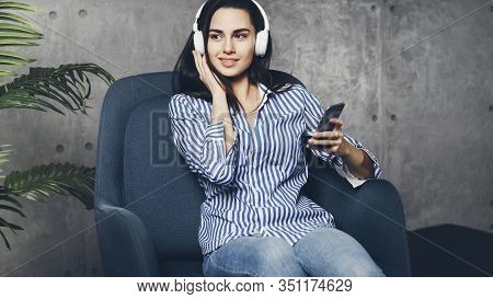 Young Woman Sitting In Room And Enjoying Music Streamed From Mobile Phone. Girl In Earphones Listeni
