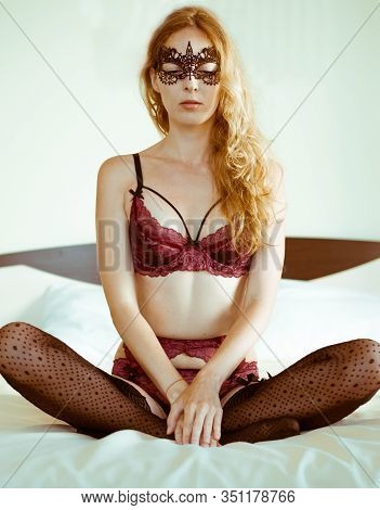 Beautiful Sexy Woman In Lace Burgundy Bra, Panties And Belt With Stockings On The Bed