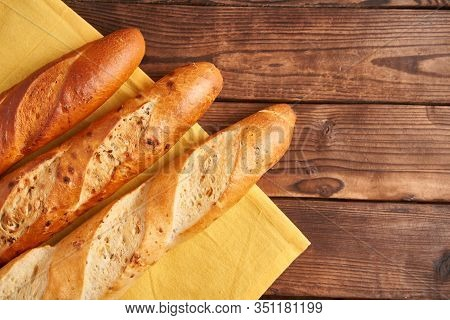 Three Crispy French Baguettes Lie Yellow Cloth Napkin Wooden Table Background Baguettes In Assortmen
