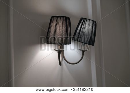 Classic Lamp On The Wall. Lighted Lamp Shade. Ray Of Light. Closeup Lamp Decorated On White Wall Bac
