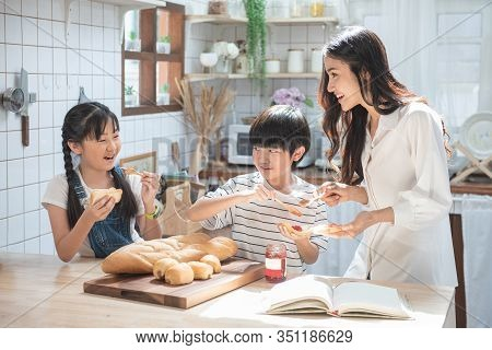 Happy Asian Family In The Kitchen. Mother And Son And Daughter Spread Strawberry Yam On Bread, Leisu