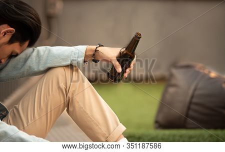 Addiction Hungover Drunk Man Hold Bottle Of Beer In Hand Sit And Inactive Sleep.unemployed Young Asi