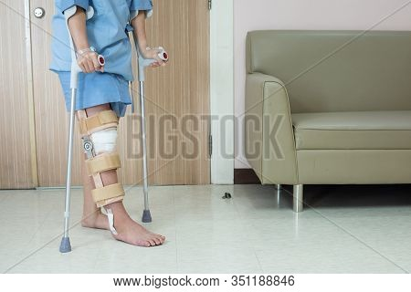 Asian Woman Patient With Knee Brace With Walking Stick And Knee Braces Support In Hospital Ward Afte