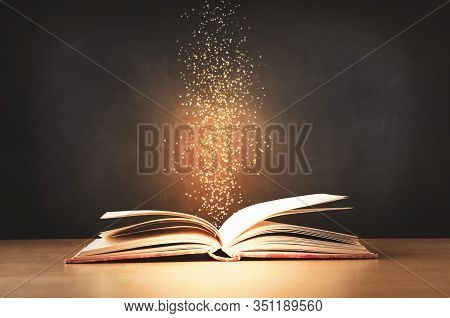 An Old, Worn, Red Text Book, Lying Opened On A Classroom Desk With Sparkles And Stars Rising Upwards