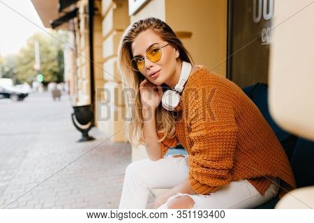 Pretty Lady In White Jeans And Brown Cardigan Looking With Interested Smile While Resting On Bench.
