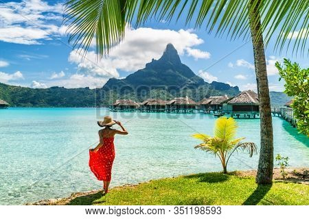 Tahiti travel holiday luxury hotel vacation tourist woman walking on Bora Bora island beach with view of Mt Otemanu in French Polynesia. High end resort with overwater bungalows villas.