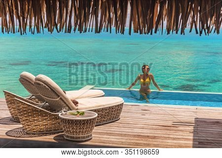 Luxury Bora Bora resort hotel woman Vacation woman relaxing in swimming pool of private hotel room overwater bungalow villa. Bikini girl on private terrace with infinity ocean view honeymoon's suite.