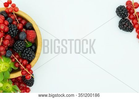 Top View Of The Wooden Bowl On The Left Of The Image With Strawberries, Redcurrants, Blueberries, Bl