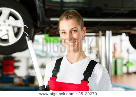 Mature man - client - and young female car mechanic looking under auto hood