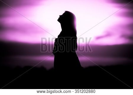 Youth Woman Soul At Pink Sun Meditation Dreaming Past Times. Silhouette In Front Of Sunset Or Sunris