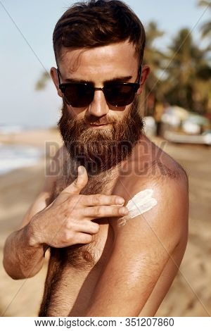 Handsome Man With Beard,  Sunbathing With Sunscreen Lotion Body In Summer. Male Fitness Model Tannin