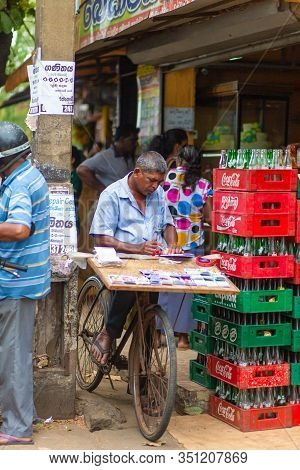 A Man On A Bicycle Sells Lottery Tickets In The Market. Poverty And Misery In Sri Lanka. Colombo / S
