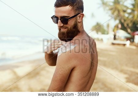 Handsome Man With Beard  Sunbathing With Sunscreen Lotion Body In Summer. Male Fitness Model Tanning
