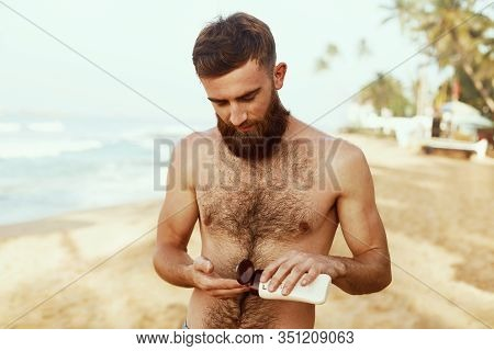 Handsome Man With Beard,sunbathing With Sunscreen Lotion Body In Summer. Male Fitness Model Tanning