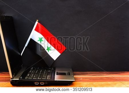 Flag Of Syria , Computer, Laptop On Table And Dark Background