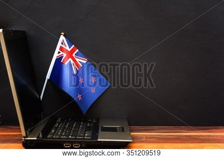 Flag Of New Zealand , Computer, Laptop On Table And Dark Background