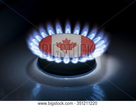 Burning Gas Burner Of A Home Stove In The Middle Of Which Is The Flag Of The Country Of Canada. Gas