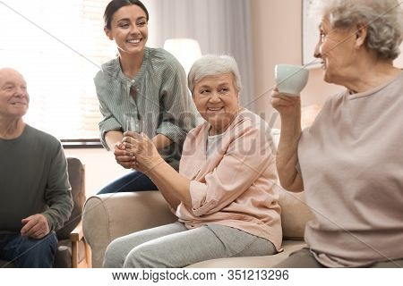 Young Woman Taking Care Of Elderly People In Living Room