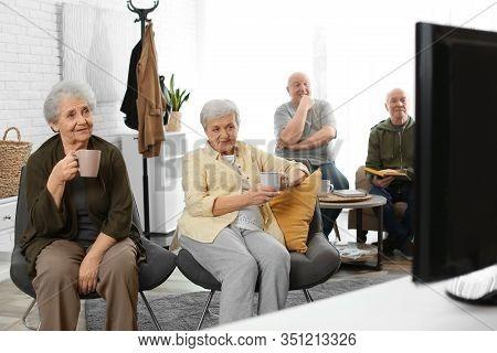 Elderly People Watching Tv In Geriatric Hospice. Senior People Care