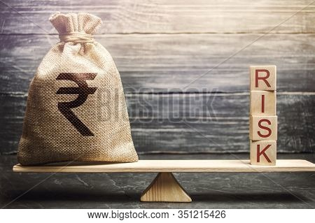 Money Bag And Wooden Blocks With The Word Risk On The Scales. Business Risk Management And Assessmen