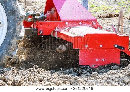 Farmer Plows The Field. Small Tractor With A Plow In The Field. Cultivation.