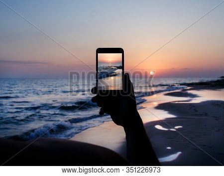 Man Takes A Sunset Photo On The Mobile Phone