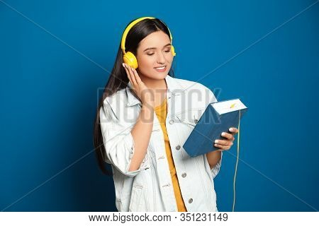 Young Woman Listening To Audiobook On Blue Background