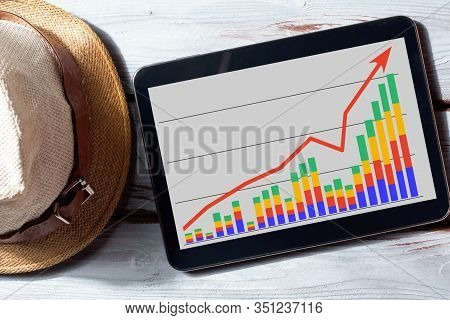 A Tablet With A Financial Schedule, A Beach Towel, Sunglasses And Shells. Business Chart. Freelancer