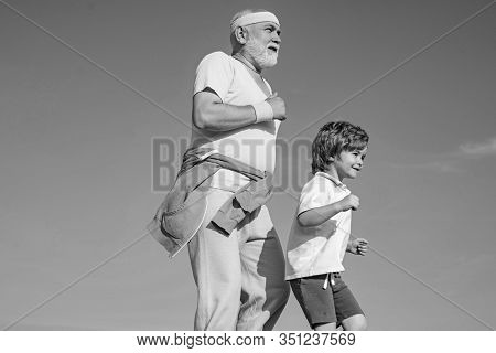 Jog And Run Marathon For Family. The Old And Young Sportsmen Running On The Road. Portrait Of Health