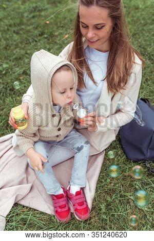 Happy Young Family, Woman Mom, Little Boy Inflates Soap Bubbles, Rest Park, Concept Parenting Child
