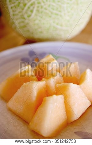 Plate Of Slices Muskmelon Cantaloupe With Blurry Whole Fruit In Background