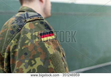German Soldier Stands In A Classroom . German Word Bundeswehr, Means German Army.