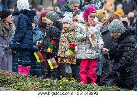 Vilnius, Lithuania - Feb 16, 2020: Children Bearing Lithuanian Flags Watch A State Ceremony To Mark
